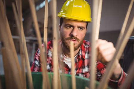 wooden stick: Carpenter looking at wooden stick in workshop
