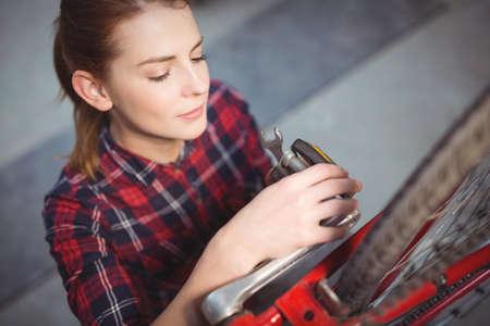 servicewoman: Female mechanic repairing a bicycle in workshop
