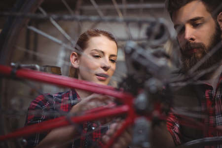 servicewoman: Mechanics repairing a bicycle in workshop