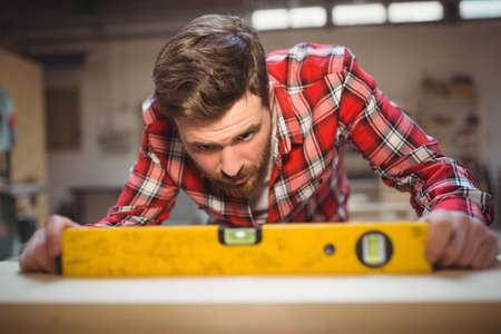 spirit level: Carpenter using spirit level to measure at workshop