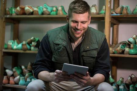 cobbler: Cobbler looking his tablet in a workshop LANG_EVOIMAGES