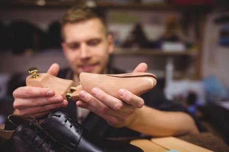 cobbler: Cobbler holding a shoe tree in workshop