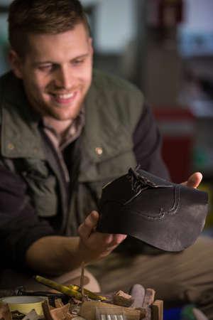 cobbler: Cobbler holding a leather material in workshop LANG_EVOIMAGES