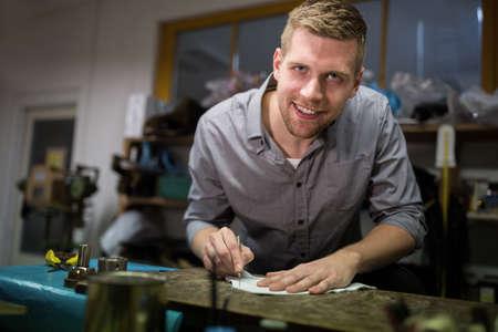 cobbler: Portrait of cobbler cutting a piece of material in workshop LANG_EVOIMAGES
