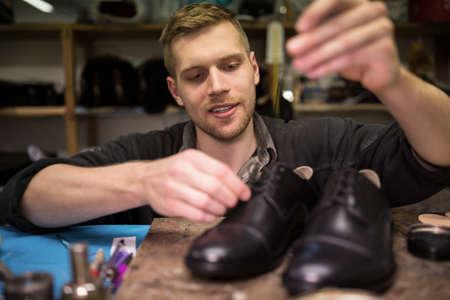 cobbler: Cobbler putting lace on shoes in workshop