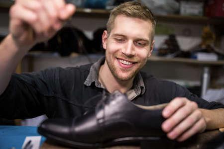 cobbler: Cobbler putting lace on shoe in workshop LANG_EVOIMAGES