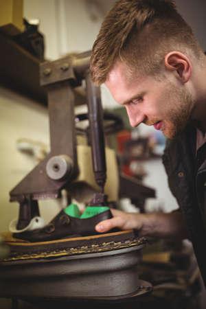 cobbler: Cobbler examining a shoe in his workshop