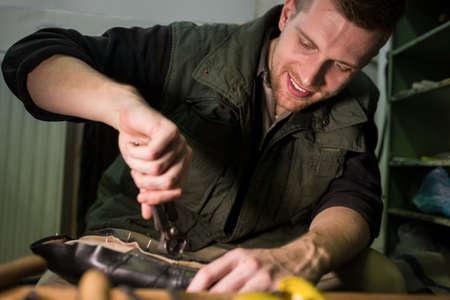 cobbler: Portrait of a smiling cobbler repairing a shoe in workshop LANG_EVOIMAGES