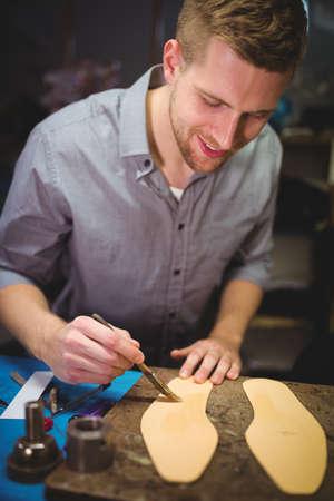 cobbler: Cobbler applying glue on insole at workshop