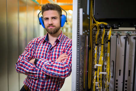 head phones: Portrait of technician with arms crossed and head phones in server room LANG_EVOIMAGES