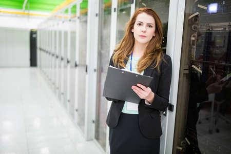 check room: Portrait of technician preparing check list in server room