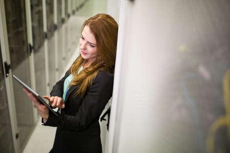 network server: Technician using digital tablet in server room