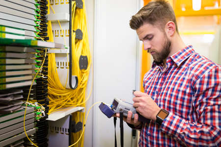 analyzer: Technician holding digital cable analyzer in server room