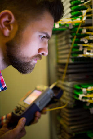 analyzer: Close-Up of technician using digital cable analyzer in server room