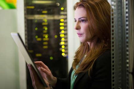 technology: Technician using digital tablet in server room