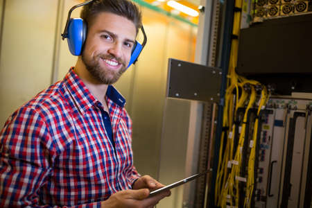 head phones: Portrait of technician in head phones using digital tablet while analyzing server in server room LANG_EVOIMAGES