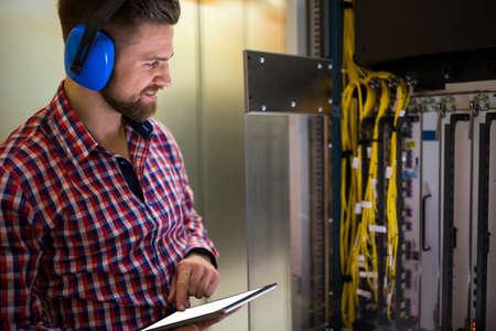 head phones: Technician in head phones using digital tablet while analyzing server in server room
