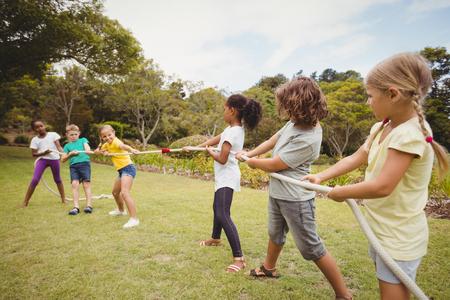 Kinder ziehen ein Seil im Tauziehen im Park
