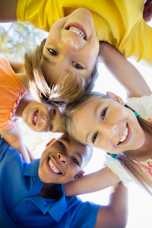 forming: smiling children forming a huddle in circle in the park Stock Photo