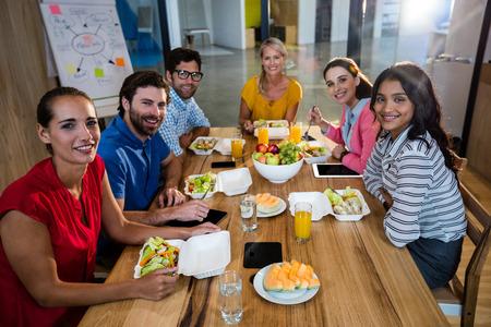Casual Business Team zusammen essen im Büro