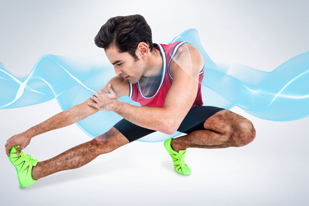 hamstring: Male athlete stretching his hamstring against grey background