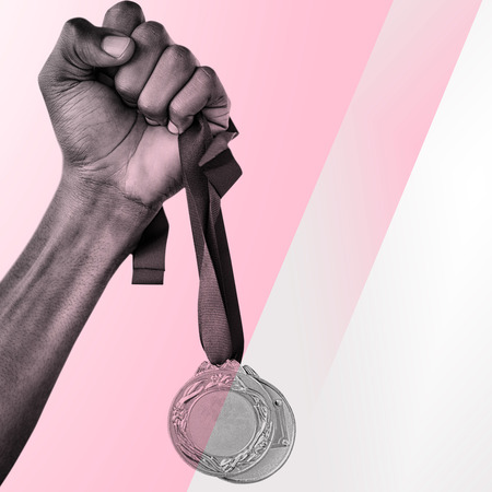 hand: Hand holding two gold medals on white background against different colors
