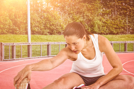 hamstring: Athlete woman stretching her hamstring against race track Stock Photo
