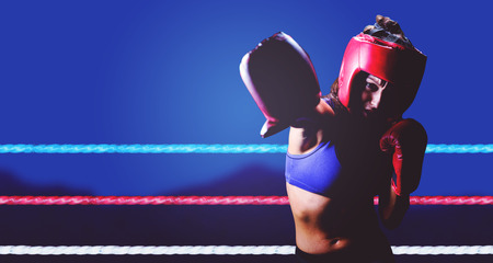 headgear: Female boxer with gloves and headgear punching against blurred mountains
