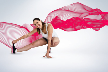 hamstring: Happy athlete woman stretching her hamstring against grey background