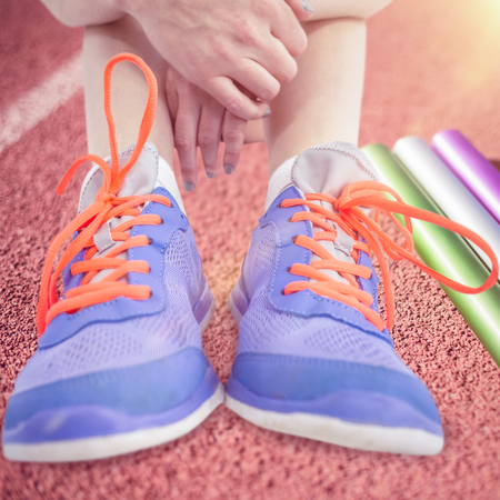 relay baton: Athlete woman sitting with sports shoes against focus of relay baton on a race track