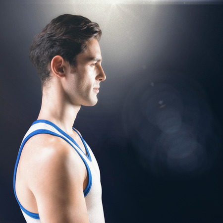 side lighting: Side view of male athlete on black background  against view of lighting