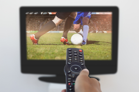 changing channel: Hand holding remote and changing channel against football players tackling for the ball on pitch