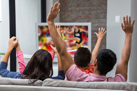Athletic man practicing show jumping against happy family rejoicing while watching tv on the sofa Stock Photo
