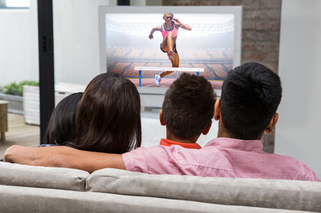 changing course: Athletic woman practicing show jumping against happy family watching tv on the sofa