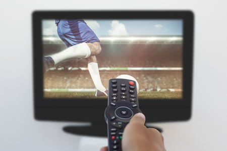 changing channel: Football player kicking ball against hand holding remote and changing channel Stock Photo