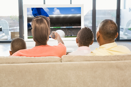 Football player kicking ball against over shoulder view of casual family watching tv photo