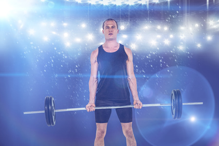 digitally generated image: Bodybuilder lifting heavy barbell weights against digitally generated image of spotlight against black background Stock Photo