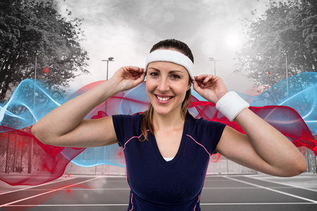 composite image: Female athlete wearing headband and wristband against composite image of tennis field on a sunny day