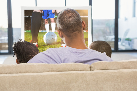 Two children sitting on sofa with their father against football players tacakling for the ball on pitch photo