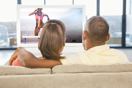 over the shoulder: Athletic woman practicing show jumping against over shoulder view of casual couple watching tv Stock Photo