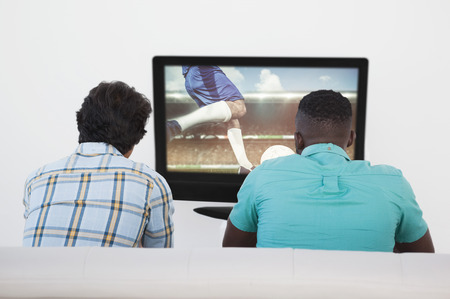 kicking ball: Football player kicking ball against two soccer fans watching tv