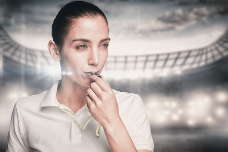 arbitrator: Female athlete blowing a whistle against sports arena