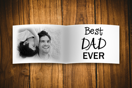smooch: Attractive smiling father with his child against overhead of wooden planks