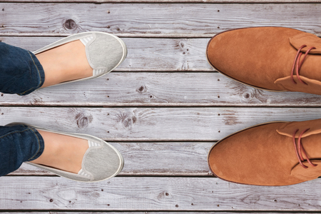 casually dressed: Casually dressed womans feet against digitally generated grey wooden planks