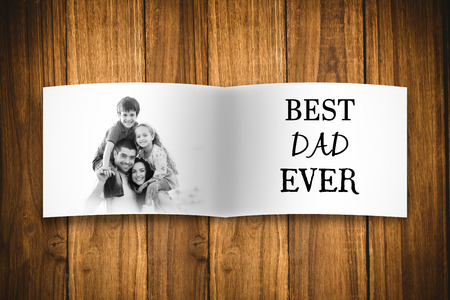 Composite image of fathers day gift and family picture against wooden planks photo