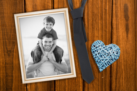 Father giving son piggyback ride against overhead of wooden planks photo