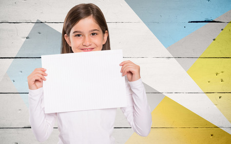 blank page: Cute little girl showing card against colored wood