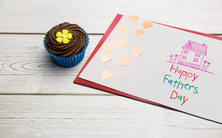 calorific: Word happy fathers day and drawn pink house against delicious cupcakes on a table Stock Photo