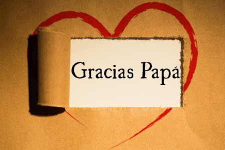 directly above: Word gracias papa against directly above shot of torn brown paper