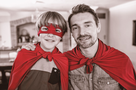 pretending: Portrait of father and son pretending to be superhero in living room at home